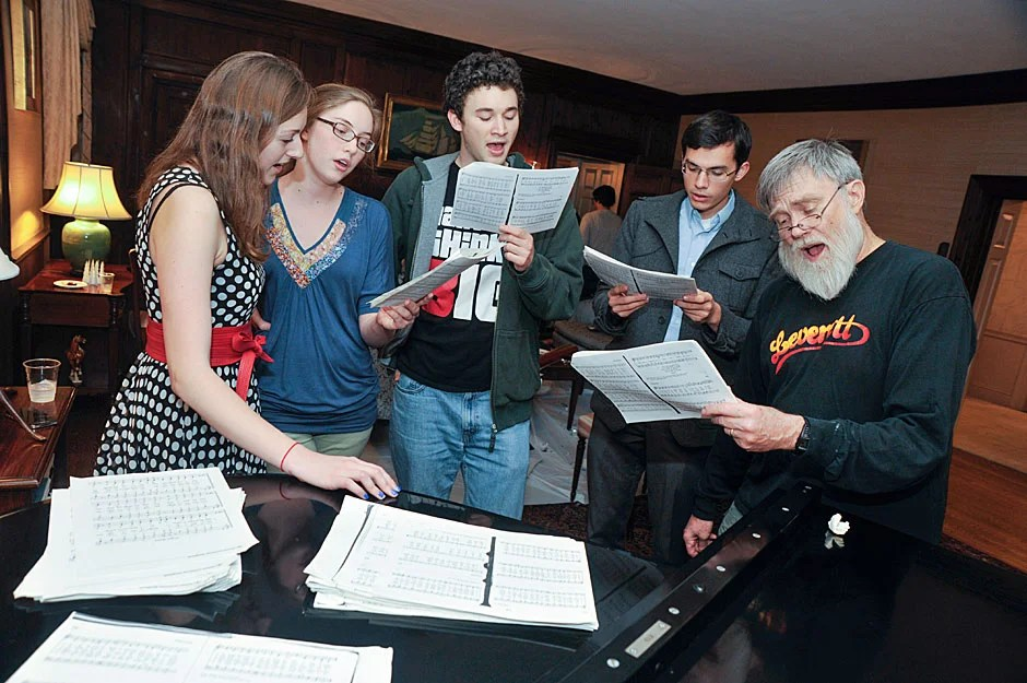 House Master Howard Georgi (right) joins student choristers for impromptu carols around the piano during the Leverett Open House. Jon Chase/Harvard Staff Photographer