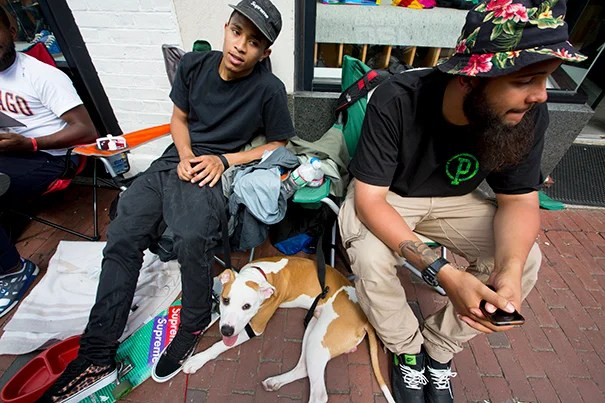 """Kamal Malik (center) and friends Max the dog, Robin Brown (right), and Corey Lewis (left) camped in front of Concepts shoe store to score limited-edition Harvard-themed sneakers (photo 1). New Yorkers David Medrano (from left), Bidhan Roy, Kevin Robles, and Alex Velazquez took a break from the sidewalk campsite to go for a ride (photo 2). Concepts' storefront, where the line for the Asics """"Three Lies"""" sneaker begins (photo 3)."""