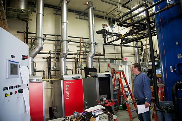 The Harvard Forest's new, super-efficient, thermal biomass system, which provides heating to five nearby buildings via wood-fired boilers, offers a functional tool for research (photos 1, 2). The woods crew focuses on taking low-quality material out of the forests for use as biomass, therefore improving the growth and quality of trees with a higher economic and ecological value (photo 3).