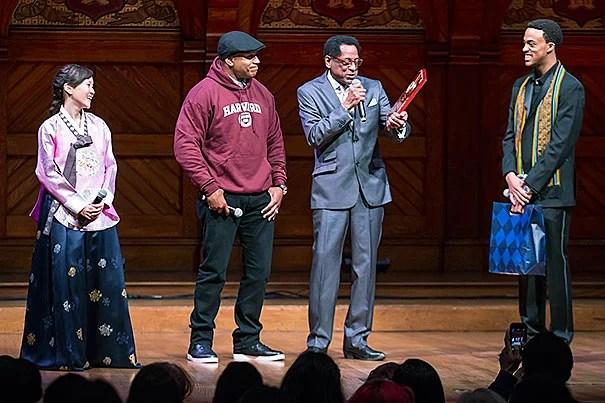 """LL Cool J (second from left) was presented  the Harvard Foundation's Artist of the Year award by S. Allen Counter. """"There's been no one more committed to young people's education than LL Cool J,"""" Counter said. Aubrey Walker '15 and Soyoung Kim '14,  co-directors of Cultural Rhythms, shared the Sanders Theatre stage during Saturday's award presentation."""