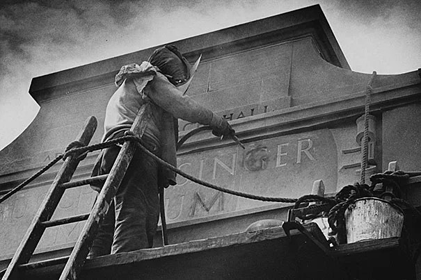 This 1958 photo shows a worker at Adolphus Busch Hall on Kirkland Street changing the name of Harvard's Germanic Museum to the Busch-Reisinger Museum — an outward sign of the museum's shifting identities in the 20th century. On paper, the official name change came in 1950.