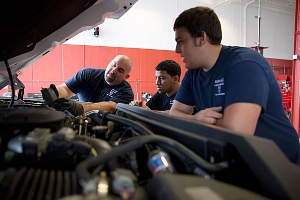 "Harvard fleet technician Luigi Criscuolo (left) works with summer interns Javon Santos (center) and Pasquale Fulginiti, who said the experience ""has given me a glimpse of what to expect when I leave here to attend the Benjamin Franklin Institute of Technology, and ultimately begin my career in automotive services."""