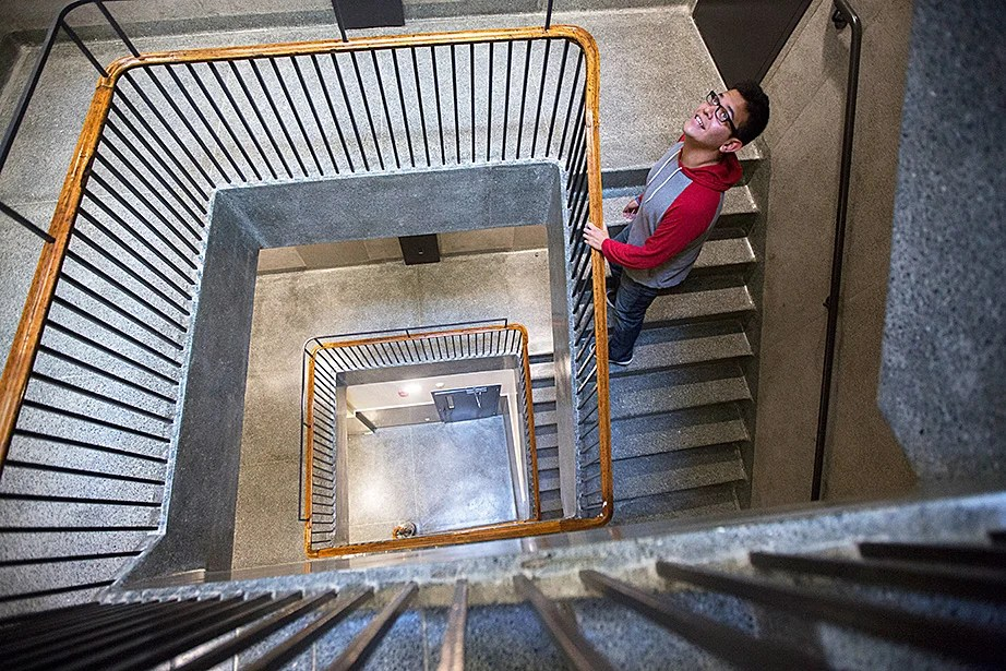 Miguel Perez-Luna climbs a historic stairwell inside McKinlock Hall. Kris Snibbe/Harvard Staff Photographer