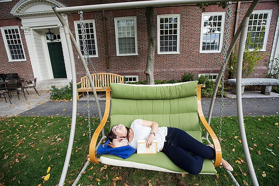 Lien Le '17 studies on a bench swing in the courtyard of McKinlock Hall. Kris Snibbe/Harvard Staff Photographer
