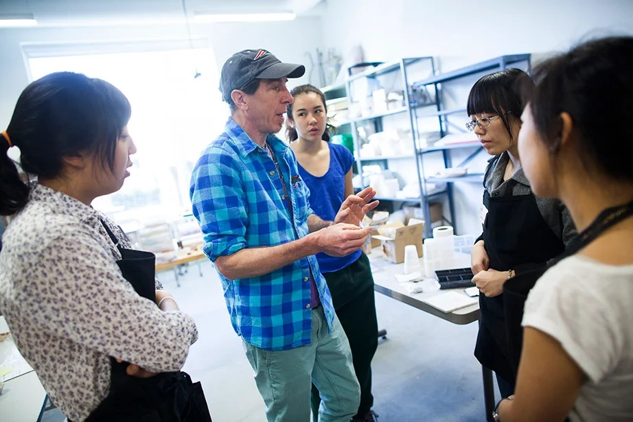 "Wayne Fuerst teaches ""Adornment: Basic Jewelry Smithing with Silver Clay"" at the Harvard Ceramics Program. Eliza Chang '16 (from left), Fuerst, Cristina Parajon '18, and Rebecca Chen '16 look at jewelry examples. Stephanie Mitchell/Harvard Staff Photographer"