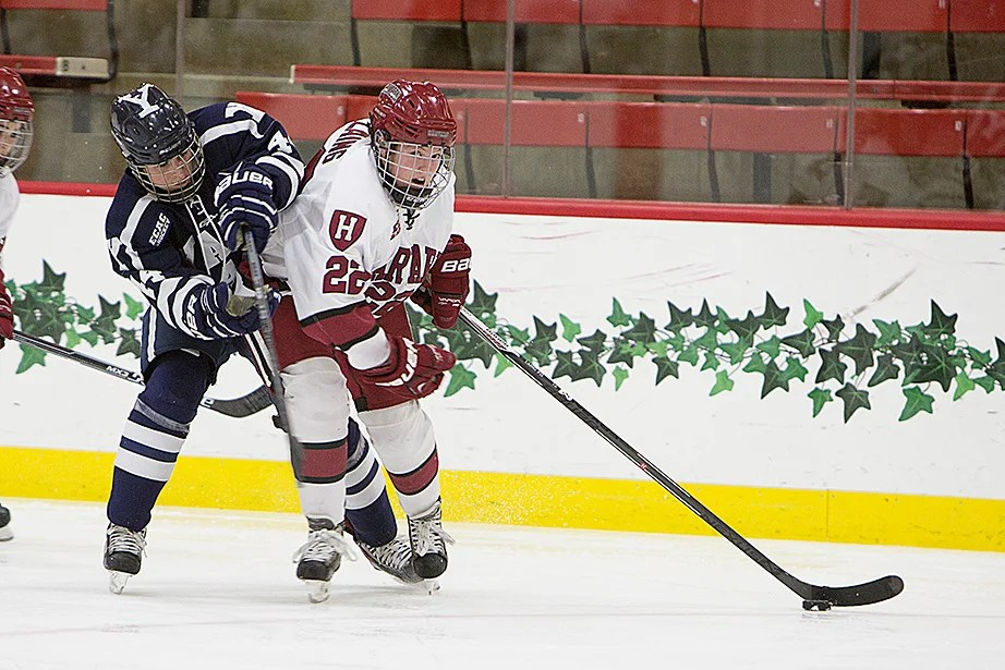 Lexie Laing '18 uses her body to protect the puck from her Yale opponent during the first ECAC quarterfinal game. Harvard won, 2-1. Laing has nine goals and 13 assists for 22 points, the fifth highest on the team. Rose Lincoln/Harvard Staff Photographer