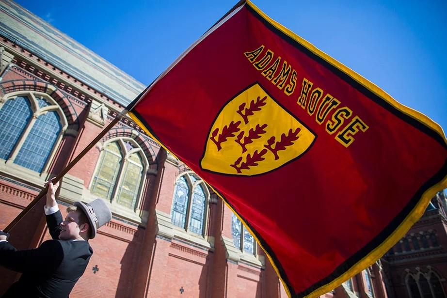 Erik Olsen '15 of Adams House waves a flag outside Memorial Hall. Stephanie Mitchell/Harvard Staff Photographer