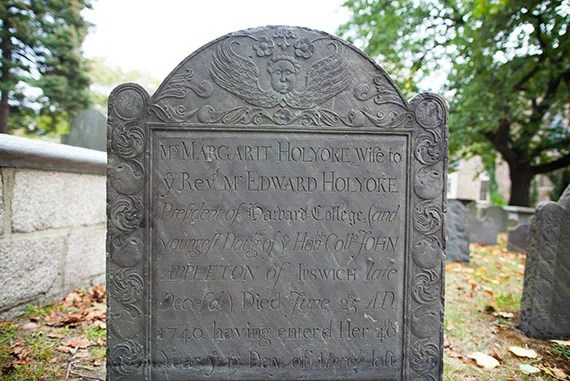 Executive Director of the Cambridge Historical Commission Charles Sullivan tours through the Old Burial Ground in Harvard Square where numerous notable Harvard figures are buried. Pictured here is a tombstone with the name Holyoke. Stephanie Mitchell/Harvard Staff Photographer