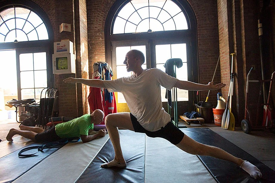 GSAS student Ben Oseroff stretches after training for the Head of the Charles. Mark Abelson, professor of ophthalmology at Harvard Medical School, planks in the background.