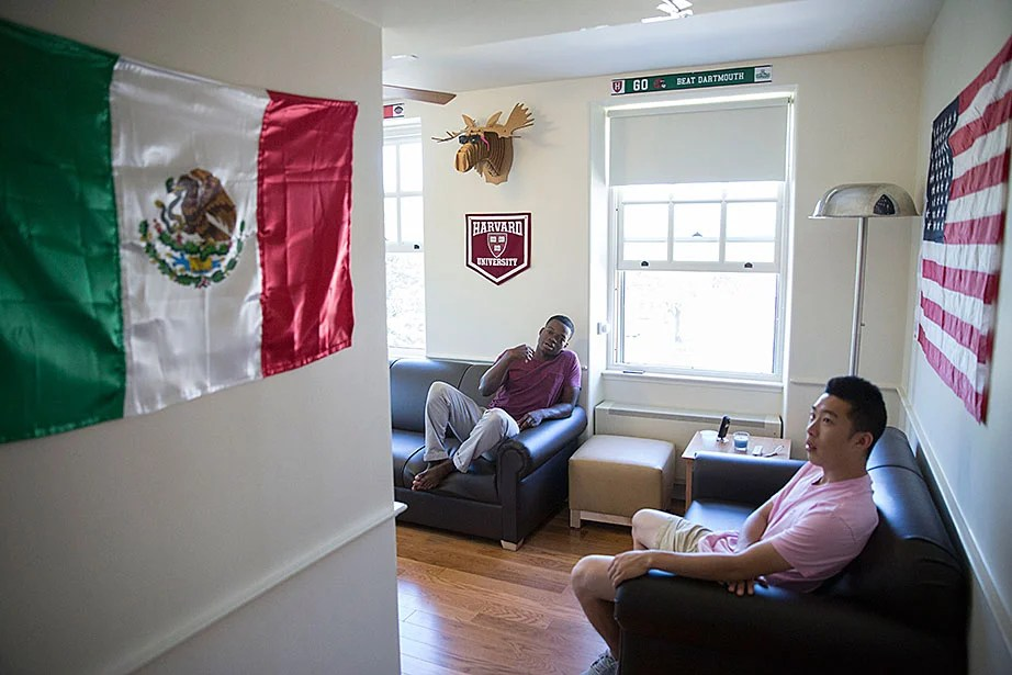 Kevin Chen '17 (pink shirt), Ayomide Opeyemi '17, and their roommates decorate their room with flags of Mexico and the United States. Kris Snibbe/Harvard Staff Photographer