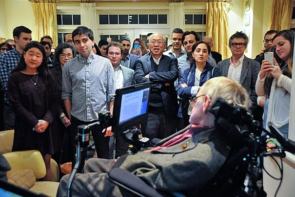 Students and faculty, including Keyon Vafa '16 (second from left), gather to view a slide show and presentation by Stephen Hawking. Cumrun Vafa, Donner Professor of Science, hosted a dinner at his home in Newton in honor of Hawking's visit to Harvard.