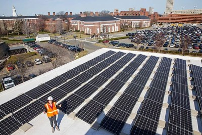 Standing on the roof of Batten Hall, Julia Musso, the energy and sustainability coordinator for Harvard Business School, shows an array of 113kW solar panels that provide energy for the HBS campus. In 2015, HBS also installed solar panels on its Travis Street building and a new solar thermal unit on the roof of Esteves Hall that uses heat from the sun to provide hot water. The University's Schools and departments have installed more than 1MW of solar panels on rooftops across Harvard's campus, including at the Harvard Athletics Complex, Canaday Hall in Harvard Yard, the Divinity School, the Graduate School of Education, Harvard Forest, and Arnold Arboretum.