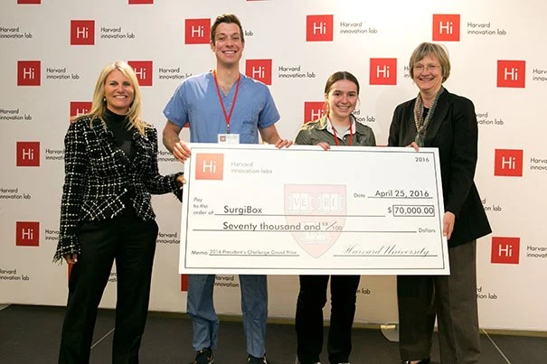 SurgiBox was named the winner of the 2016 President's Challenge. Jodi Goldstein (left), director of the Harvard i-lab, and Harvard President Drew Faust (right) presented the award check to SurgiBox team members Christopher Murray and Madeline Hickman.