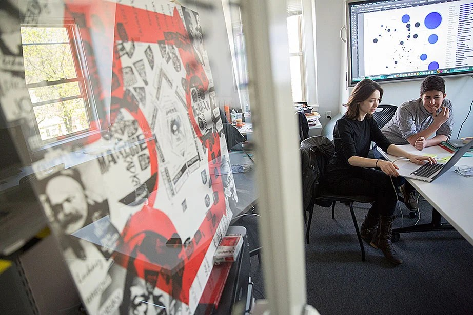 """Krystelle Denis (left), HGSD '15, a researcher and designer, and Jessica Yurkofsky, principal and creative technologist, work on data visualizations inside the metaLAB office and studios. They are in the early stages of a metaLAB project called """"Curricle,"""" which will offer novel ways to search and discover patterns in course registration, student interests, and the history of the liberal arts."""