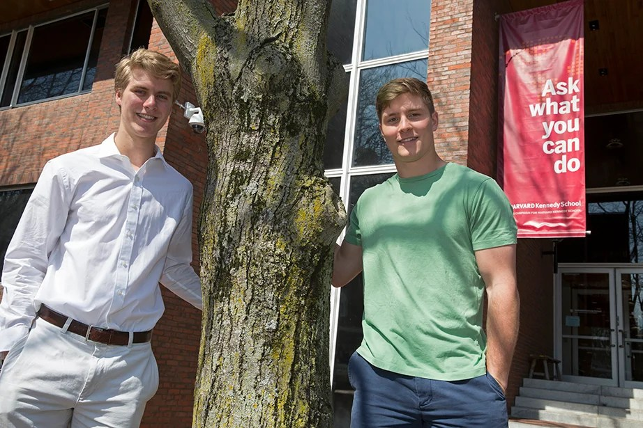 "Harvard sophomores Nicholas (left) and Beau Bayh '18 are twins from Indiana. Both have an interest in politics and social service, as well as athletics. They stand at the entrance to the Harvard Kennedy School in front of a sign that reflects their desire to serve: ""Ask what you can do."" Jon Chase/Harvard Staff Photographer"