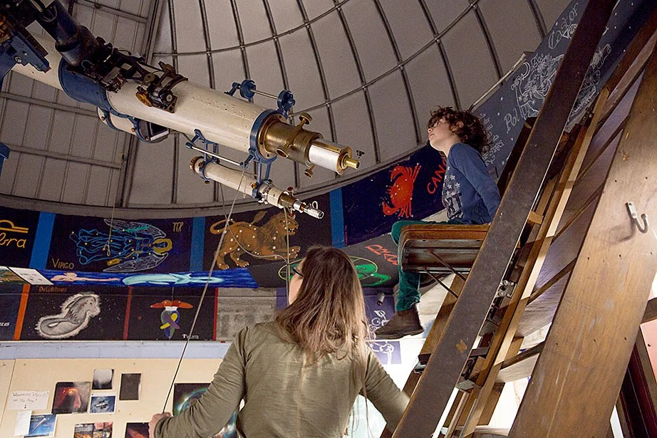 Michael Goldberg peers through the Loomis-Michael Telescope while Allyson Bieryla, manager of the Astronomy Lab and the Clay Telescope, helps him understand how it works.