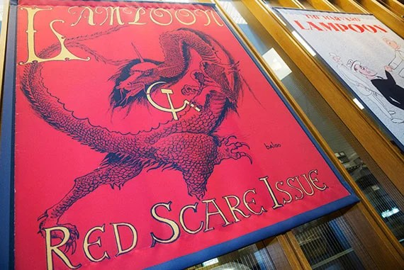 "The cover of the ""Red Scare Issue"" from 1950—featuring a red dragon with a hammer and sickle stuck in its claws—is just one of many Lampoon-related treasures on display through October 2. Kris Snibbe/Harvard Staff Photographer"
