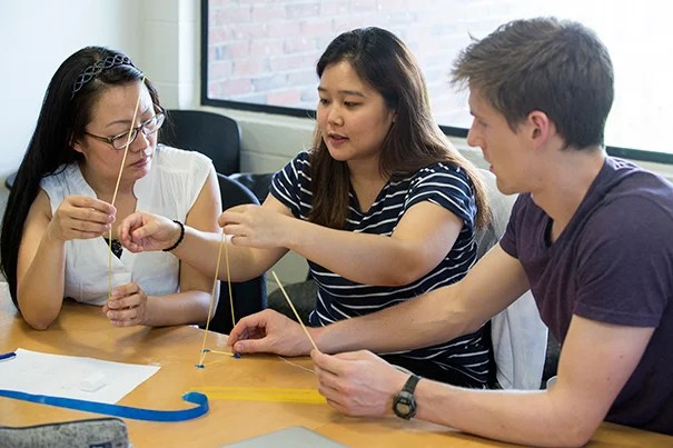 Irene Liu (left), Eunice Park, and Sam Fogel use spaghetti and tape to support a marshmallow during an exercise. Jon Chase/Harvard Staff Photographer