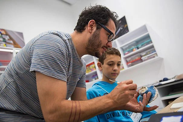 Salvador Jiménez Flores, (left) Harvard Ceramics Artist-in-Residence, Ceramics Program, Office for the Arts works with Mehdi Kayi, Boston Latin School 9th grader, and other students participating in the summer explorations program inside the Ed Portal at Harvard. Kris Snibbe/Harvard Staff Photographer