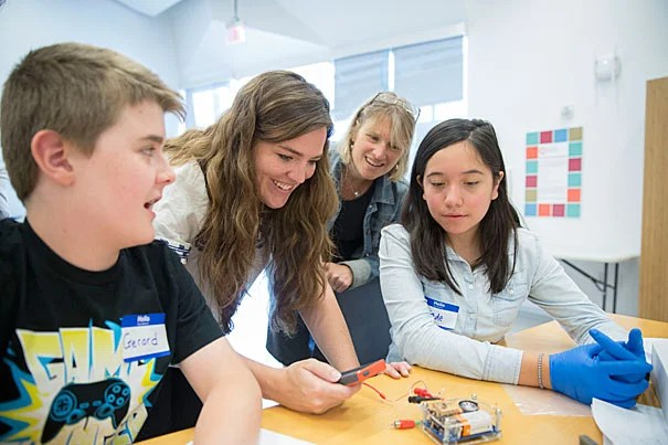 Gerard McGrath, (from left) rising 8th grader at the Boston Latin School, Katie Schmalkuche í16, Emily Henson, Program Manager, Harvard X for Allston, Susan Johnson, Manager of Teaching and Curriculum for the Education Portal and Jade Diaz, rising 8th grader, Saint Columbkille School in Brighton, learn about the basics of neuroscience and electricity in the brain using the curriculum of the Fundamentals of Neuroscience HarvardX course at the Ed Portal in Allston. Kris Snibbe/Harvard Staff Photographer