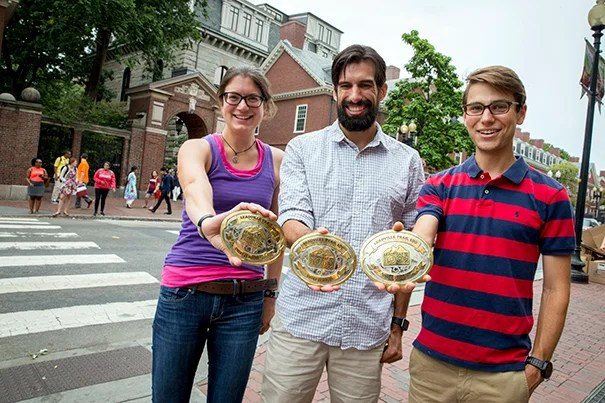 Harvard University students and training partners Maartje Bastings (left), Charles Hornbaker, and Max Darnell present their gold belt buckles for finishing the Leadville 100 Trail Run in Colorado in under 25 hours.