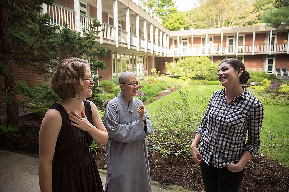 "Center for the Study of World Religions residents (from left) Melissa Coles, a student at Harvard Divinity School; the Ven. Changshen Shi Wang, visiting assistant professor at HDS; and Sara Klingenstein, a student at the Graduate School of Arts and Sciences, chat in the center's courtyard. ""Residents are a microcosm of the larger community at HDS: a non-sectarian school of religious and theological studies that is home to a diverse community of scholars and practitioners,"" Coles said."