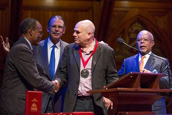 University Professor William Julius Wilson congratulates David Simon as Glenn Hutchins, and University Professor Henry Louis Gates, Jr. look on. Jon Chase/Harvard Staff Photographer
