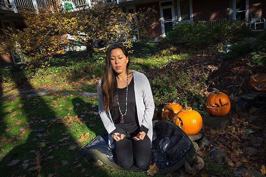 Jack-o'-lanterns look on as Vicky Lee, M.Div., practices Kriya Yoga mudras and breathing exercises in the CSWR courtyard. Lee, a Christian, incorporates yoga and meditation into her spiritual practice.