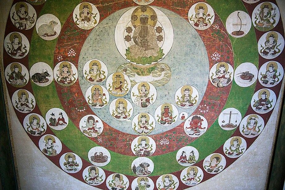 """""""Shakyamuni Buddha Surrounded by Heavenly Circles,"""" a 17th-century mandala of gouache and ink on silk, is displayed in the CSWR common room."""