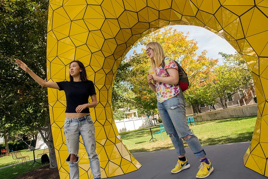 "Diana Yan, GSD '18 (left), and Susie Clements '19 pose with the art installation ""Grid Structure"" outside Gund Hall at Harvard Graduate School of Design. Kris Snibbe/Harvard Staff Photographer"