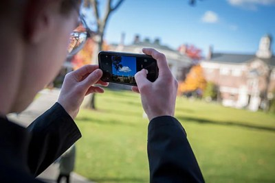 "Jasper Johnston '20, creator of the Instagram photography project ""100 Days of Harvard,"" snaps a photo from the steps of Longfellow Hall in Radcliffe Yard."
