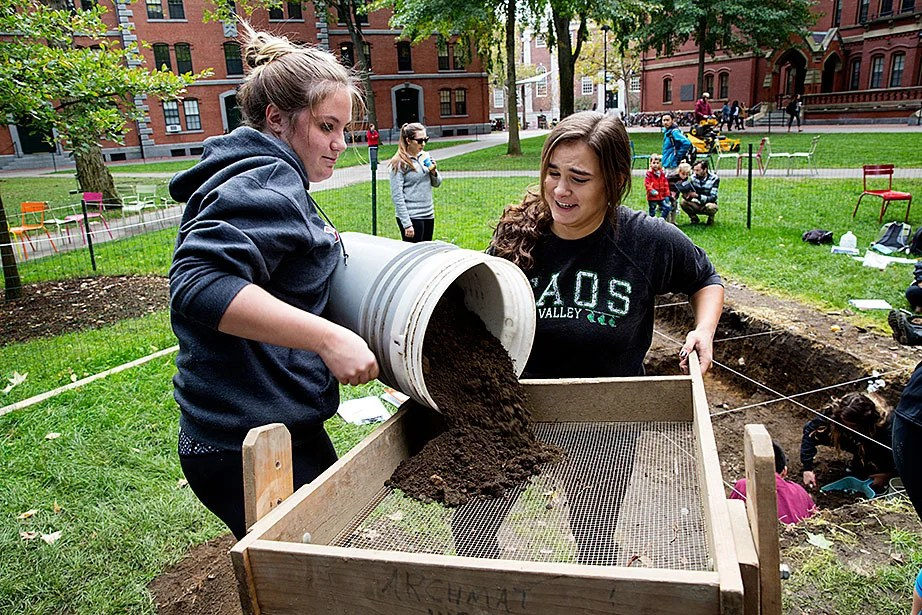Julia Thomas '17 (left) empties a bucket of dirt into a sifter as Betsy Peinado '19 looks on. Moving the sifter vigorously back and forth causes the dirt to fall through, while keeping pebbles and artifacts on the screen.