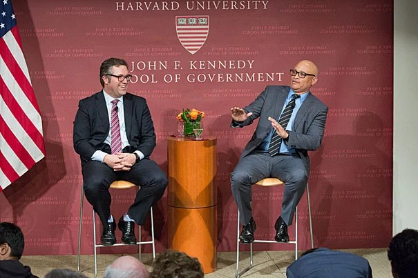 """Director of the Shorenstein Center Nicco Mele (left) laughs at a retort by comedian Larry Wilmore during their talk at the Harvard Kennedy School. """"I do find it ironic that we elect a reality show star as president, and you invite a fake journalist to give the Theodore H. White lecture on it,"""" said Wilmore."""