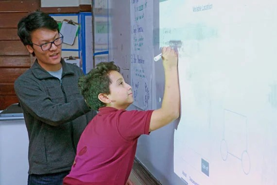Chris Zhou '19, an economics concentrator, helps Gardner Pilot Academy sixth-grader Jonathan Gonzalez write JavaScript functions on the classroom's whiteboard during a Digital Literacy Project lesson. (Photo by Adam Zewe/SEAS Communications.)