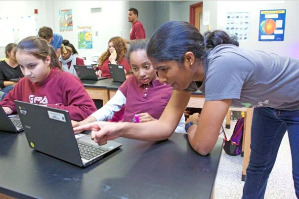 Suriya Kandaswamy '20, who intends to concentrate in computer science, explains a coding problem to Gardner Pilot Academy seventh-grader Diamonique Marmoucha during a Digital Literacy Project lesson.