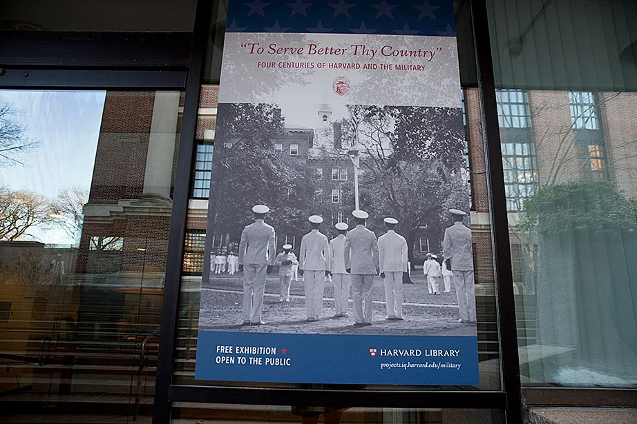 A sign welcoming visitors to the exhibit at Pusey Library shows a group of cadets from the first graduating class of the Naval Training School at Harvard in 1942.