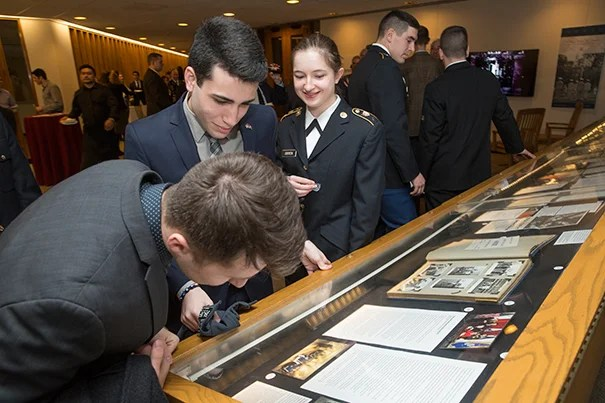 "Reception for the Pusey Library archives exhibit ""To Serve Better Thy Country"". Boris Davidov '19, front center, and Alannah O'Brien '19, front right, look over the exhibit. Attendees: University leadership TBC; undergraduate ROTC cadets and midshipmen; student veterans; Harvard University Veterans Organization and Alumni Organization members; faculty with ties to military; HPAC staff; University Archives staff. Jon Chase/Harvard Staff Photographer"