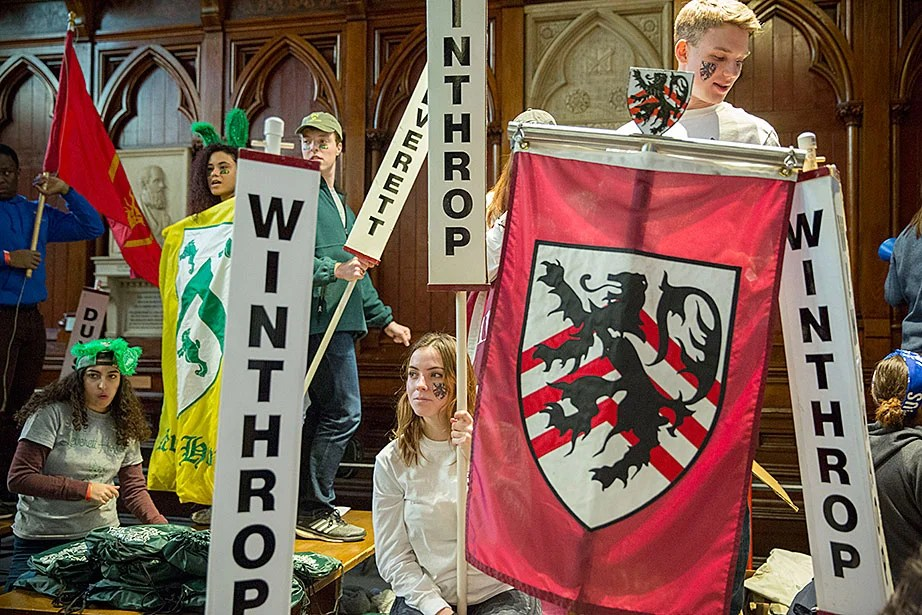 Isabel Wagner '18 welcomes students to Pforzheimer House while celebrating Housing Day inside Annenberg Hall as Trevor Noon '18 (upper right) holds a banner. Camille N'Diaye-Muller '18 (far left) holds a Leverett House banner and wears bunny ears. Kris Snibbe/Harvard Staff Photographer