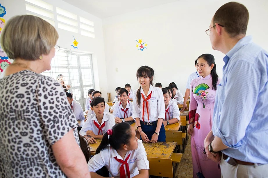 Drew Faust (from left) asks Trần Thị Ngọc Hân a question while teacher Vo Thi Mong Trinh looks on. Ben Wilkinson '98 helps translate.