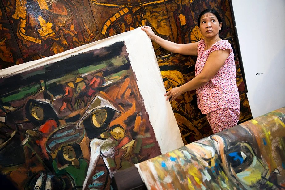 In the Hanoi studio of veteran and artist Pham Luc in Hanoi, Dao Thi Lien (pictured) arranges his works for display during Drew Faust's visit.