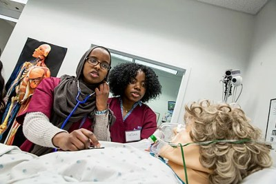 Urban Science Academy students Nadia Abdirahman (left) and Tatiana Figaro practice taking vitals during the 12-week MedScience program, a Harvard Medical School initiative for high school students considering a career in medicine.