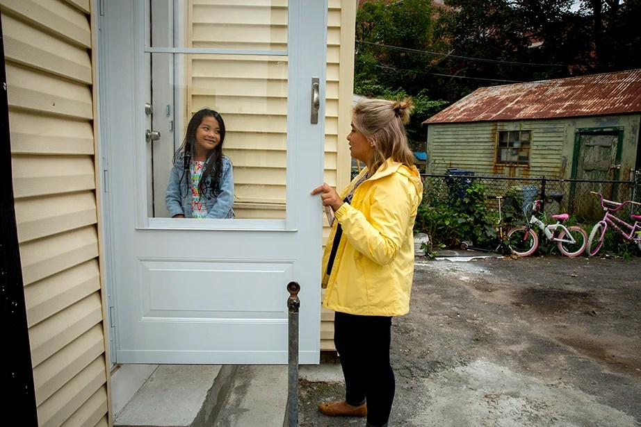 """Aileen Navarrete walks 8-year-old Thao Nguyen home from the bus stop. """"I don't like the outside of my house,"""" Thao said. """"I do,"""" replied Navarrete. """"It's the color of my coat."""""""
