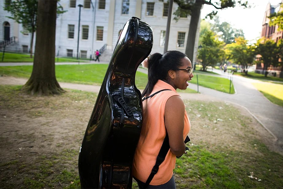 Carrying her cello across the Yard, Danielle Davis '21 arrives to collect her key. Stephanie Mitchell/Harvard Staff Photographer