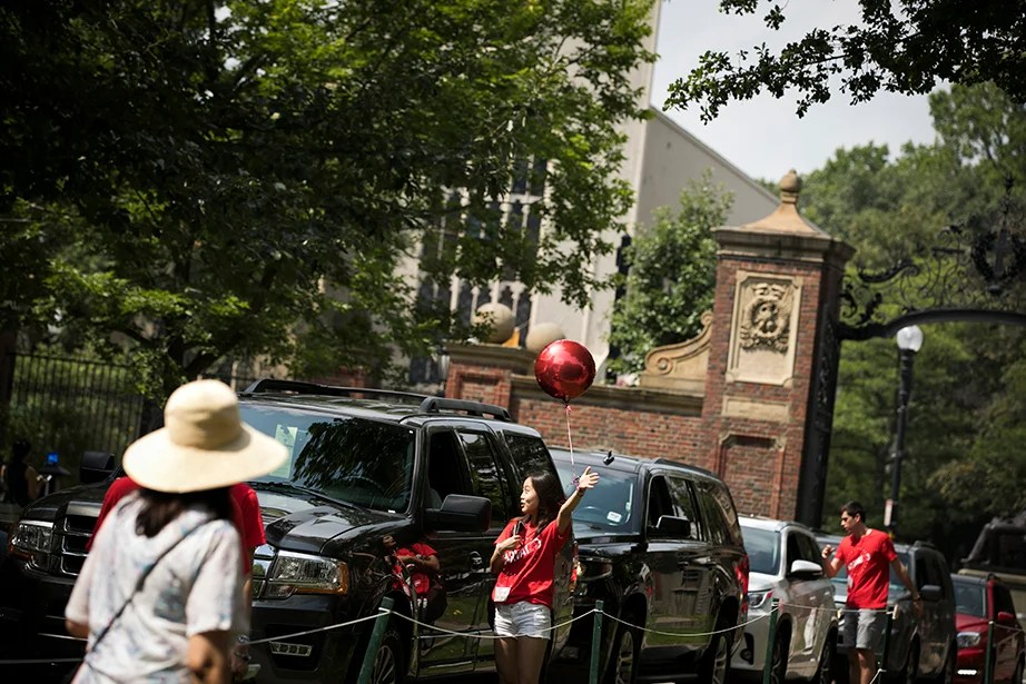 Yena Cho '20 (center) helps direct families to the residence halls in the Yard. Stephanie Mitchell/Harvard Staff Photographer