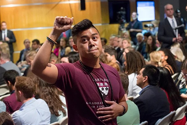 HGSE student Tony Delarosa raises a fist in protest as Betsy DeVos speaks.