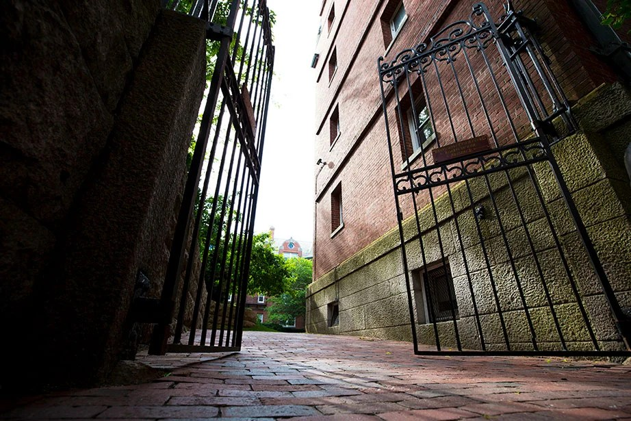 Randolph Courtyard is part of Adams House at Harvard University. Imposing black wrought-iron gates guard the entrance on Linden Street.