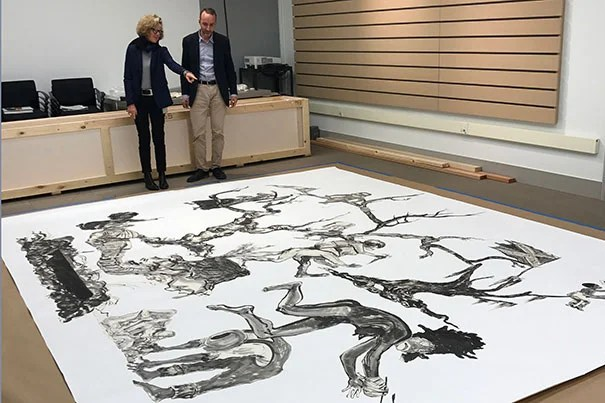 "Harvard Art Museums curators Mary Schneider Enriquez and Edouard Kopp view Kara Walker's ""U.S.A. Idioms"" at the museums' Somerville Research Center."