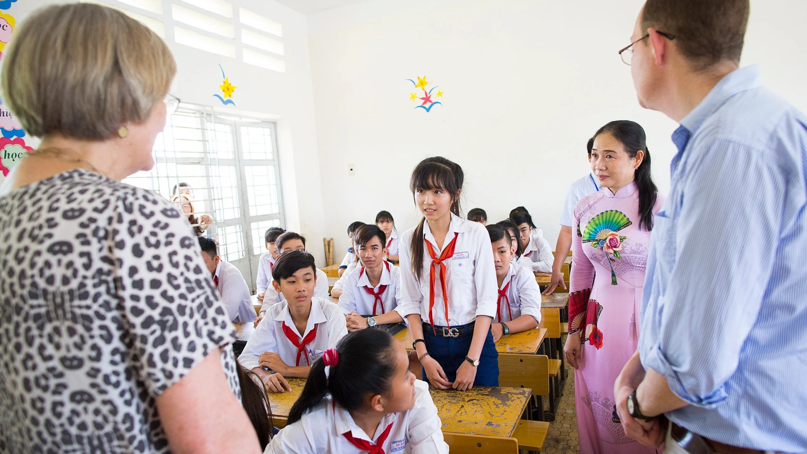 Children in a Vietnamese classroom talk with Harvard President Drew.