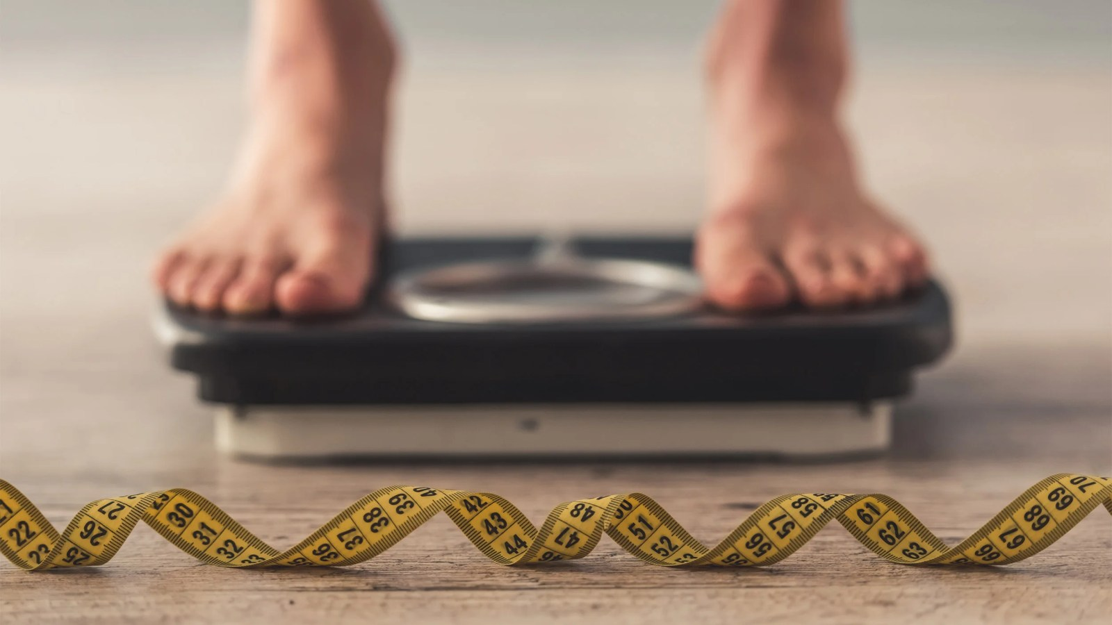 woman feet standing on weigh scales,