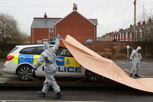 A police car being taken away by military personnel